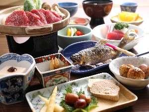 飛騨牛の陶板焼きをメインとした夕食になります。川魚の塩焼も人気の一品です。(一例)