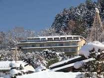 綿帽子をかぶった木々に囲まれる当館。高台からの眺めは格別です。